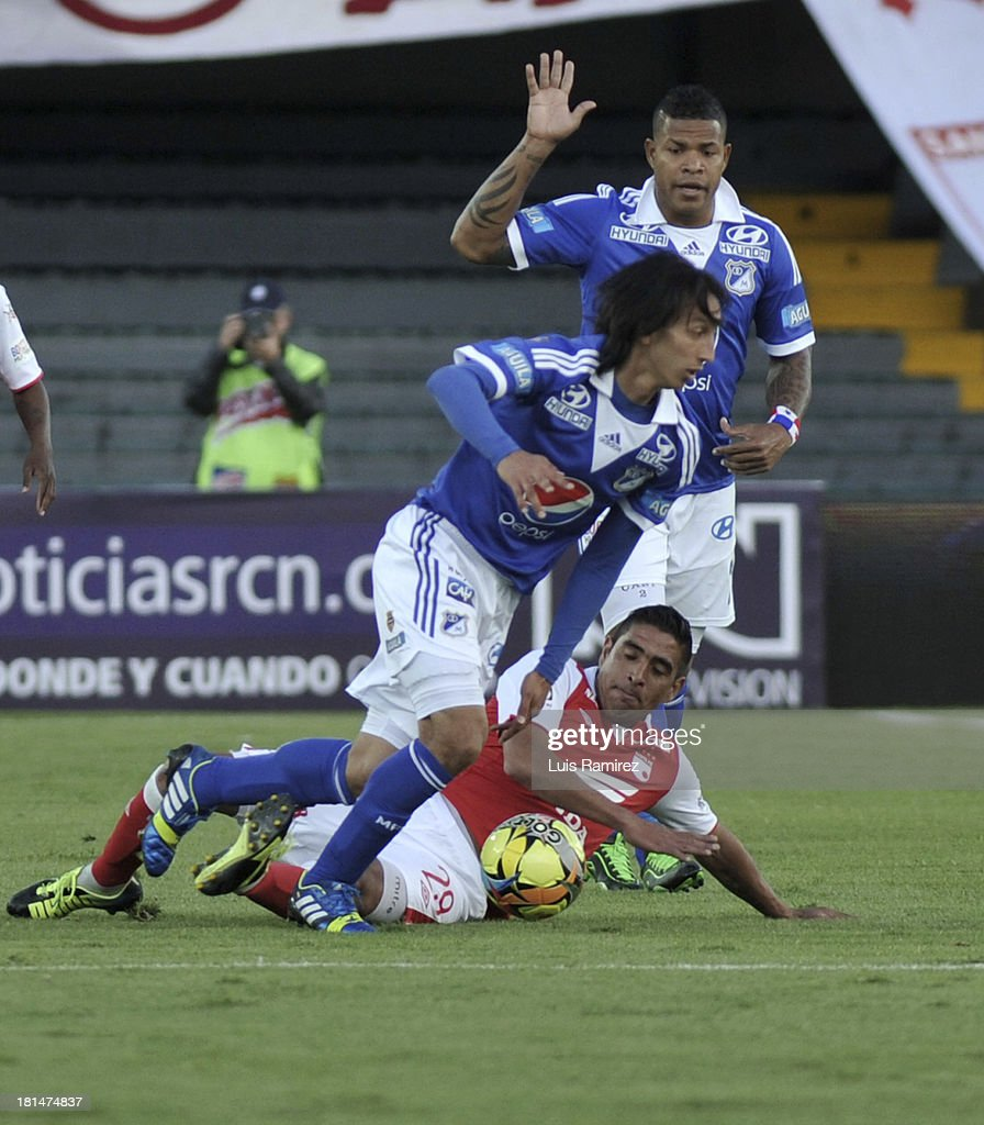 Gonzalez Renteria of Independiente Santa Fe fights for the ball with Rafael Robayo and Roman Torres of Millonarios during a match between Independiente Santa Fe and Millonarios as part of the Liga Postobon II at Nemesio Camacho Stadium on September 21, 2013 in Bogota, Colombia.