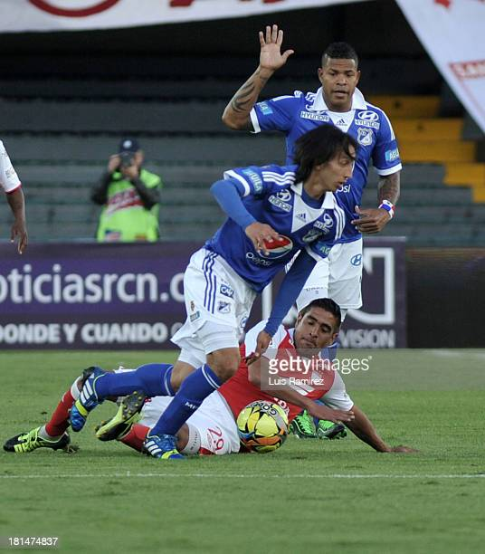 Gonzalez Renteria of Independiente Santa Fe fights for the ball with Rafael Robayo and Roman Torres of Millonarios during a match between...