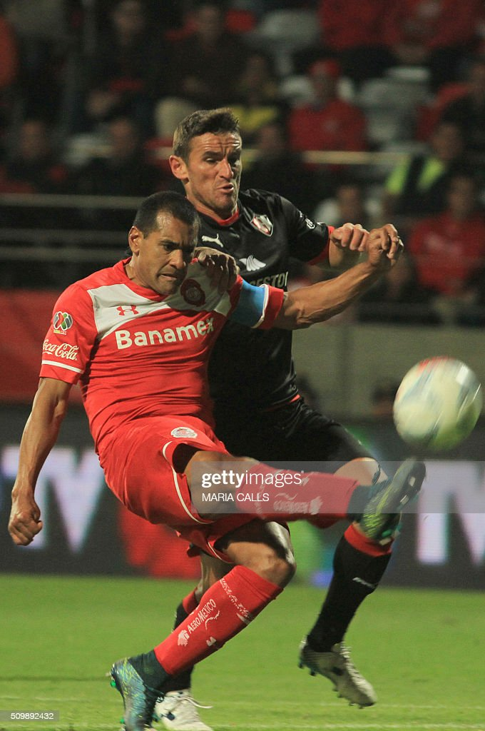 Gonzalo Bergessio (R) of Atlas vies for the ball with Paulo da Silva of Toluca during the Mexican Clausura 2016 Tournament at the Nemesio Diez stadium on February 12, 2016, in Toluca ,Mexico. / AFP / MARIA CALLS