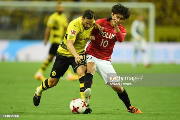 Gonzalo Castro of Borussia Dortmund and Yosuke Kashiwagi of Urawa Red Diamonds compete for the ball during the preseason friendly match between Urawa...