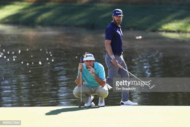 Gonzalo FdezCastano of Spain lines up a putt on the 13th green as Graham DeLaet of Canada looks on during the first round of the Travelers...