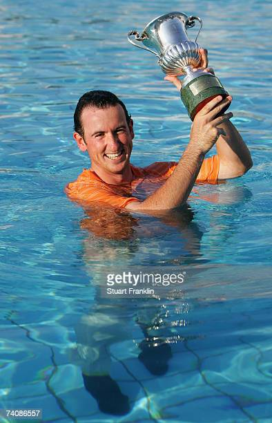 Gonzalo Fernandez Castano of Spain poses with the trophy after being thrown in the pool after winning The Telecom Italian Open Golf at The Castello...