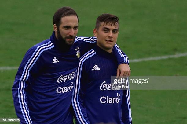 Gonzalo Higuain of Argentina and teammate Paulo Dybala walk in the field during a training session at Alberto Gallardo Stadium on October 04 2016 in...