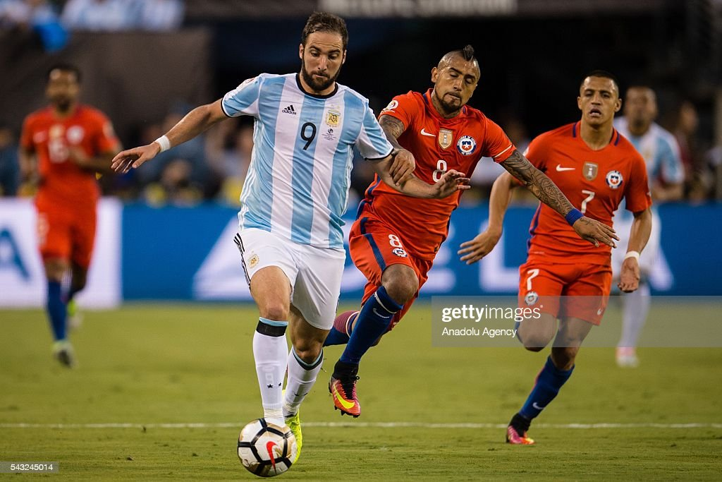 Gonzalo Higuain (L) of Argentina struggle for the ball against Arturo Vidal (R) of Chile during the championship match between Argentina and Chile at MetLife Stadium as part of Copa America Centenario 2016 on June 26, 2016 in East Rutherford, New Jersey, USA.