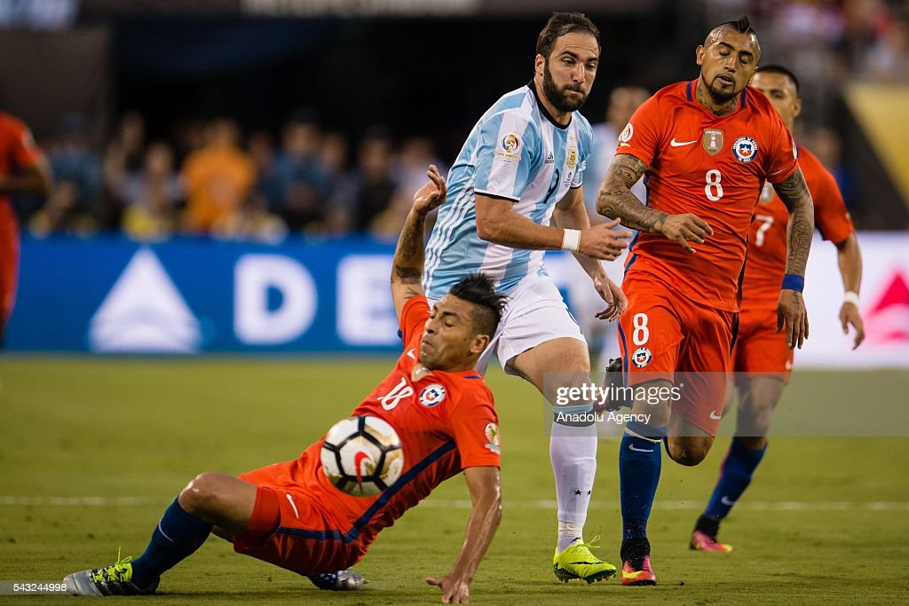 Gonzalo Higuain (C) of Argentina struggle for the ball against Gonzalo Jara (L) and Arturo Vidal (R) of Chile during the championship match between Argentina and Chile at MetLife Stadium as part of Copa America Centenario 2016 on June 26, 2016 in East Rutherford, New Jersey, USA.