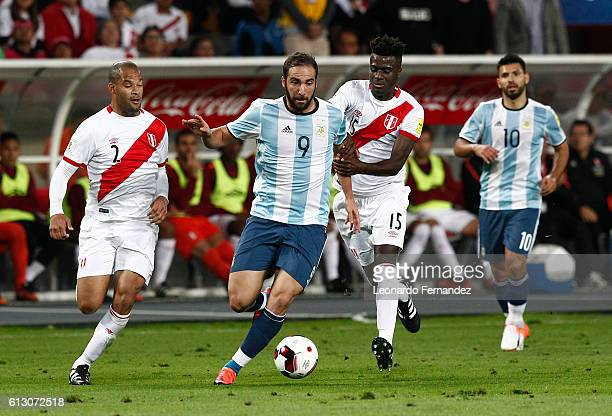 Gonzalo Higuain of Argentina struggles for the ball with Alberto Rodriguez and Christian Ramos of Peru during a match between Peru and Argentina as...