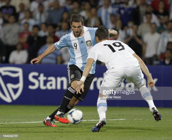 Gonzalo Higuain of Argentina struggles for the ball with Andres Scotti of Uruguay during a match between Argentina and Uruguay as part of the South...