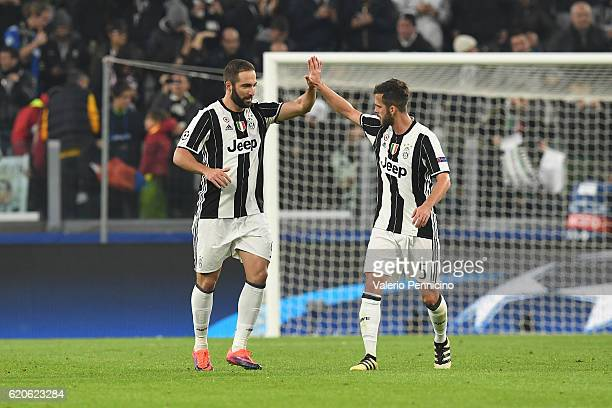 Gonzalo Higuain of Juventus celebrates after scoring the opening goal from the penalty spot with team mate Miralem Pjanic during the UEFA Champions...