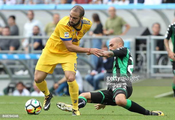 Gonzalo Higuain of Juventus competes for the ball with Paolo Cannavaro of US Sassuolo Calcio during the Serie A match between US Sassuolo and...