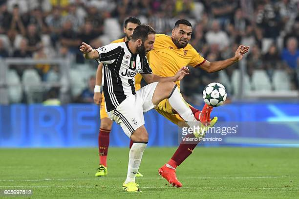 Gonzalo Higuain of Juventus FC competes with Gabriel Mercado of Sevilla FC during the UEFA Champions League Group H match between Juventus FC and...