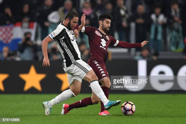Gonzalo Higuain of Juventus FC competes with Marco Benassi of FC Torino during the Serie A match between Juventus FC and FC Torino at Juventus...