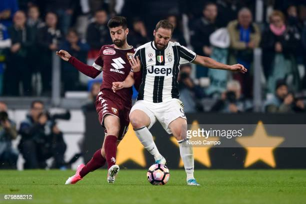 Gonzalo Higuain of Juventus FC competes with Marco Benassi of Torino FC during the Serie A football match between Juventus FC and Torino FC Final...