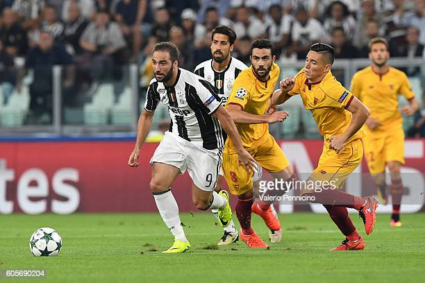 Gonzalo Higuain of Juventus FC in action against Vicente Iborra and Matas Kranevitter of Sevilla FC during the UEFA Champions League Group H match...