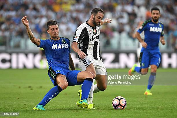 Gonzalo Higuain of Juventus FC is challenged by Francesco Acerbi of US Sassuolo during the Serie A match between Juventus FC and US Sassuolo at...