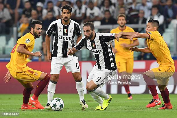 Gonzalo Higuain of Juventus FC is challenged by Matias Kranevitter of Sevilla FC during the UEFA Champions League Group H match between Juventus FC...