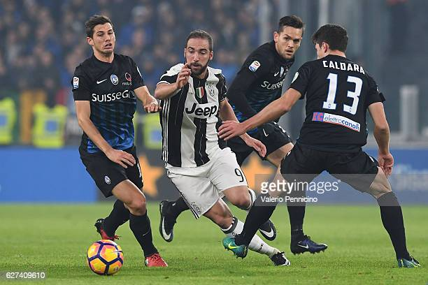Gonzalo Higuain of Juventus FC is challenged by Remo Freuler and Mattia Caldara of Atalanta BC during the Serie A match between Juventus FC and...