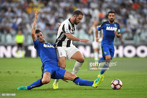 Gonzalo Higuain of Juventus FC is tackled by Francesco Acerbi of US Sassuolo during the Serie A match between Juventus FC and US Sassuolo at Juventus...