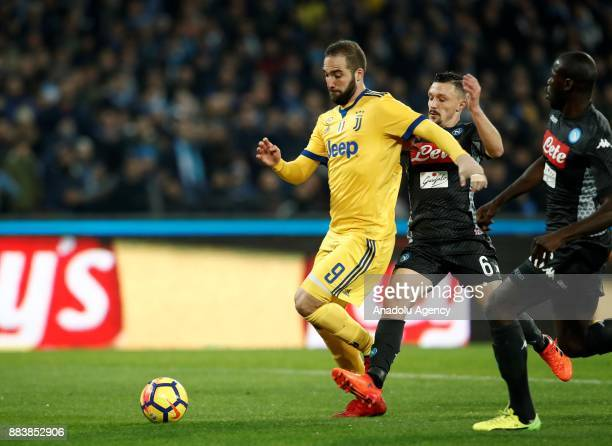 Gonzalo Higuain of Juventus in action against Mario Rui and Kalidou Koulibaly of SSC Napoli during the Serie A football match between SSC Napoli and...