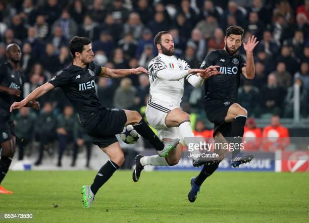 Gonzalo Higuain of Juventus in action between Ivan Marcano and Felipe Augusto de Almeida Monteiro of FC Porto during the UEFA Champions League Round...