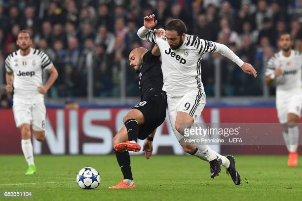 Gonzalo Higuain of Juventus is challenged by Andre Andre of FC Porto during the UEFA Champions League Round of 16 second leg match between Juventus...