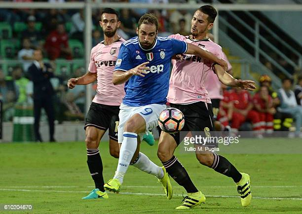 Gonzalo Higuain of Juventus is challenged by Giancarlo Gonzalez and Edoardo Goldaniga during the Serie A match between US Citta di Palermo and...