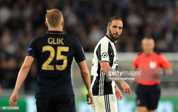 Gonzalo Higuain of Juventus looks back and speaks with Kamil Glik of AS Monaco during the UEFA Champions League Semi Final second leg match between...
