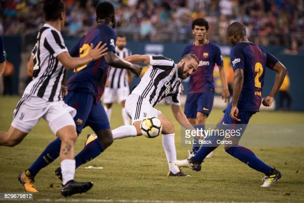 Gonzalo Higuain of Juventus tries to muscle the ball into the goal against Marlon Santos of Barcelona during the International Champions Cup match...