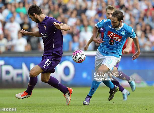 Gonzalo Higuain of Napoli competes for the ball with Davide Astori of Fiorentina during the Serie A match between SSC Napoli and ACF Fiorentina at...