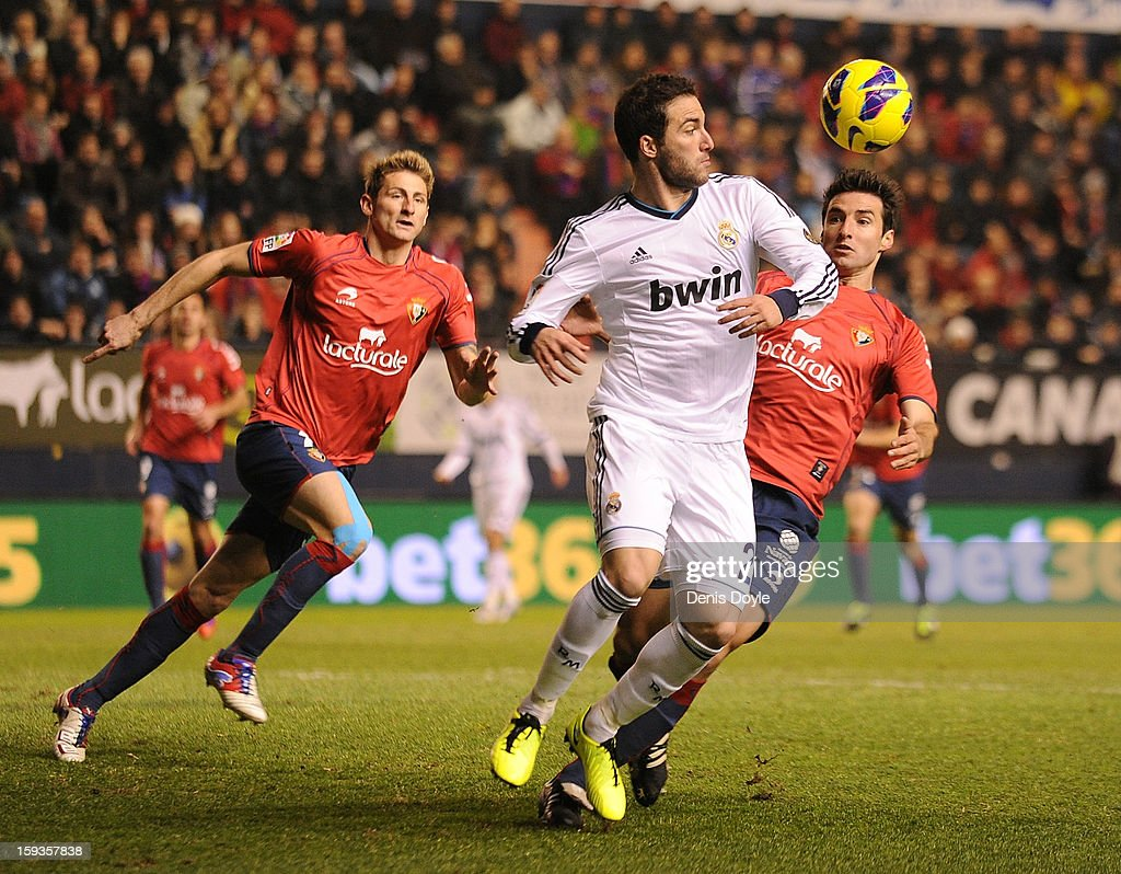 Gonzalo Higuain (L) of of Real Madrid is tackled by Marc Bertran (R) of Osasuna during the La Liga match between Osasuna and Real Madrid at estadio Reino de Navarra on January 12, 2013 in Pamplona, Spain.