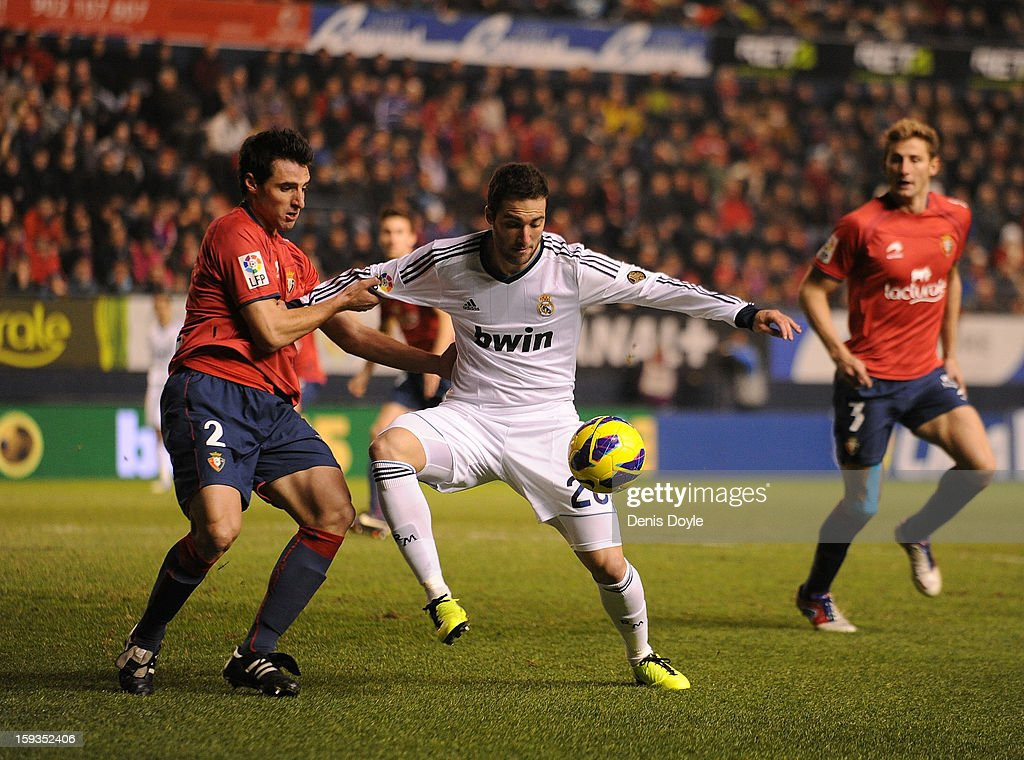 Gonzalo Higuain (R) of of Real Madrid is tackled by Ruben Gonzalez of Osasuna during the La Liga match between Osasuna and Real Madrid at estadio Reino de Navarra on January 12, 2013 in Pamplona, Spain.