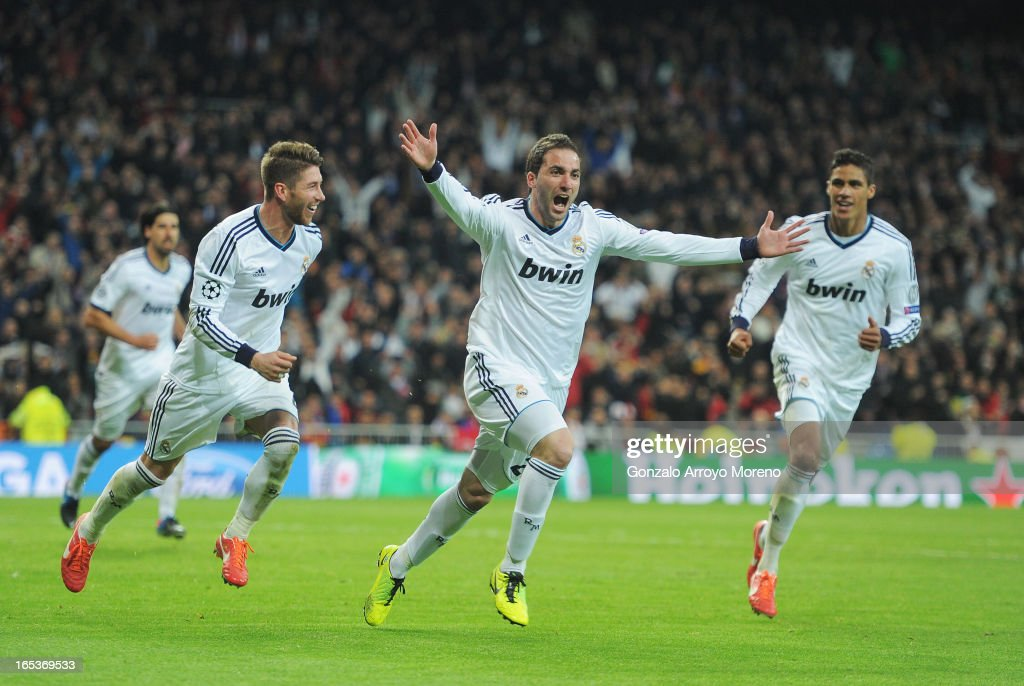 Gonzalo Higuain (C) of Real Madrid celebrates his team's third goal with <a gi-track='captionPersonalityLinkClicked' href=/galleries/search?phrase=Sergio+Ramos+-+Jugador+de+f%C3%BAtbol&family=editorial&specificpeople=491009 ng-click='$event.stopPropagation()'>Sergio Ramos</a> (L) and Raphael Varane during the UEFA Champions League Quarter Final first leg match between Real Madrid and Galatasaray at Estadio Santiago Bernabeu on April 3, 2013 in Madrid, Spain.