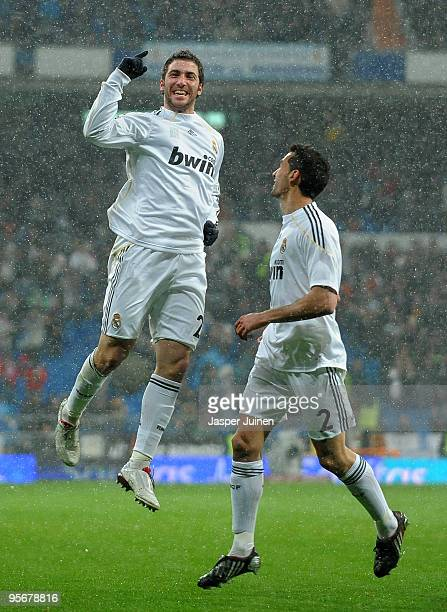 Gonzalo Higuain of Real Madrid celebrates scoring his sides opening goal with his teammate Alvaro Arbeloa during the La Liga match between Real...