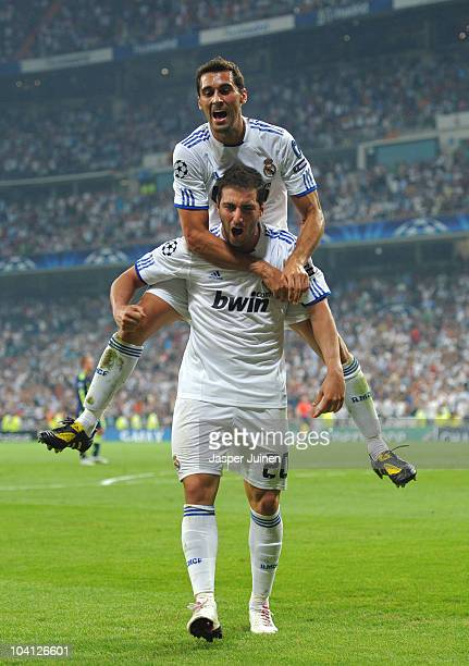 Gonzalo Higuain of Real Madrid celebrates scoring his sides second goal with his teammate Alvaro Arbeloa during the UEFA Champions League group G...