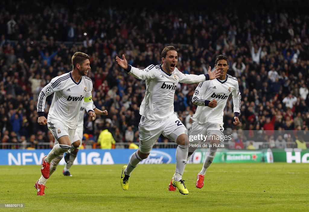 Gonzalo Higuain (C) of Real Madrid celebrates with team-mates Sergio Ramos (L) and Raphael Varane after scoring their team's third goal during the UEFA Champions League Quarter Final match between Real Madrid and Galatasaray at Estadio Santiago Bernabeu on April 3, 2013 in Madrid, Spain.