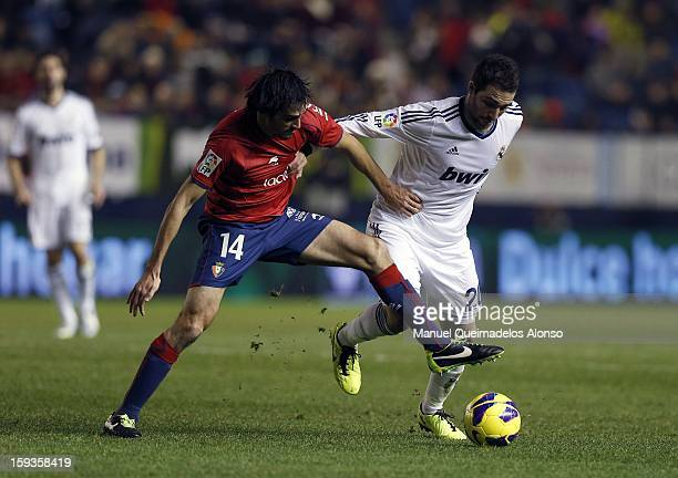 Gonzalo Higuain of Real Madrid CF duels for the ball with Alejandro Arribas of CA Osasuna during the La Liga match between CA Osasuna and Real Madrid...
