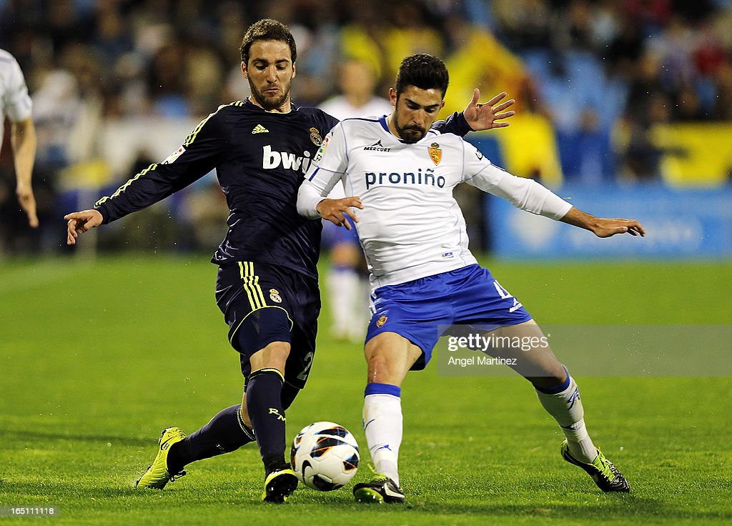 <a gi-track='captionPersonalityLinkClicked' href=/galleries/search?phrase=Gonzalo+Higuain&family=editorial&specificpeople=651523 ng-click='$event.stopPropagation()'>Gonzalo Higuain</a> of Real Madrid competes for the ball with <a gi-track='captionPersonalityLinkClicked' href=/galleries/search?phrase=Alvaro+Gonzalez+-+Soccer+Player&family=editorial&specificpeople=2261829 ng-click='$event.stopPropagation()'>Alvaro Gonzalez</a> of Real Zaragoza during the La Liga match between Real Zaragoza and Real Madrid at La Romareda on March 30, 2013 in Zaragoza, Spain.