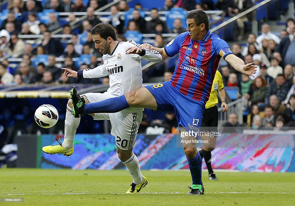 Gonzalo Higuain of Real Madrid competes for the ball with Sergio Ballesteros of Levante during the La Liga match between Real Madrid and Levante at Estadio Santiago Bernabeu on April 6, 2013 in Madrid, Spain.