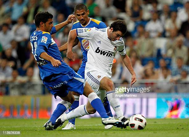 Gonzalo Higuain of Real Madrid duels for the ball with Miguel Torres of Getafe during the La Liga match between Real Madrid and Getafe at Estadio...