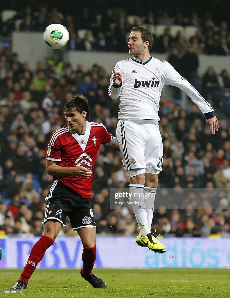 Gonzalo Higuain of Real Madrid heads the ball against Jonathan Vila of Celta de Vigo during the round of 16 Copa del Rey second leg match between Real Madrid and Celta de Vigo at Estadio Santiago Bernabeu on January 9, 2013 in Madrid, Spain.