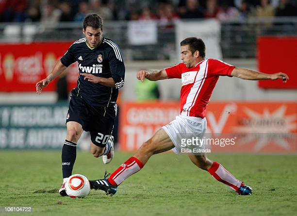 Gonzalo Higuain of Real Madrid is challenged by Carles Martinez of Real Murcia during the Copa del Rey match between Real Murcia and Real Madrid at...