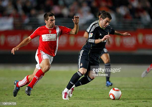 Gonzalo Higuain of Real Madrid is chased by Carles Martinez of Real Murcia during the Copa del Rey match between Real Murcia and Real Madrid at Nueva...