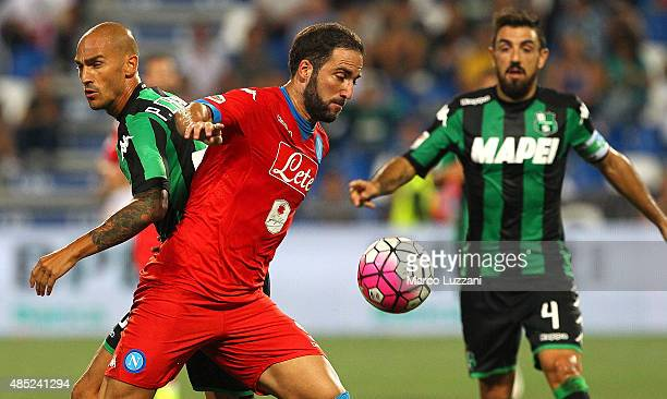 Gonzalo Higuain of SSC Napoli competes for the ball with Paolo Cannavaro of US Sassuolo Calcio during the Serie A match between US Sassuolo Calcio...