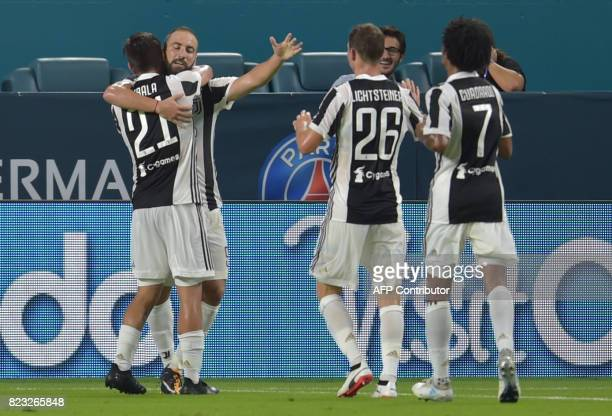 Gonzalo Higuaín of Juventus is embraced by teammate Paulo Dybala after scoring a goal against Paris SaintGermain during their International Champions...