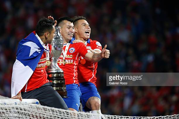 Gonzalo Jara Gary Medel and Eduardo Vargas of Chile celebrate with the trophy after winning the 2015 Copa America Chile Final match between Chile and...