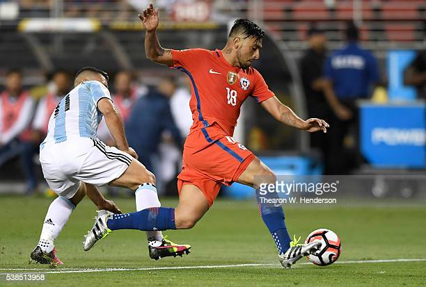 Gonzalo Jara of Chile dribbles the ball past Sergio Aguero of Argentina during the 2016 Copa America Centenario Group match play between Argentina...