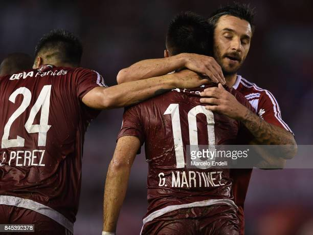 Gonzalo Martinez of River Plate celebrates with teammates Ignacio Scocco and Enzo Perez after scoring the second goal of his team during a match...