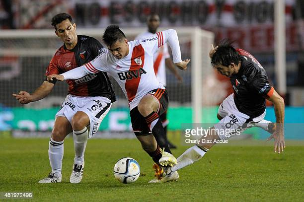 Gonzalo Martinez of River Plate struggles for the ball with Luis Garnier and Matias Ballini of Colon de Santa Fe during a match between River Plate...