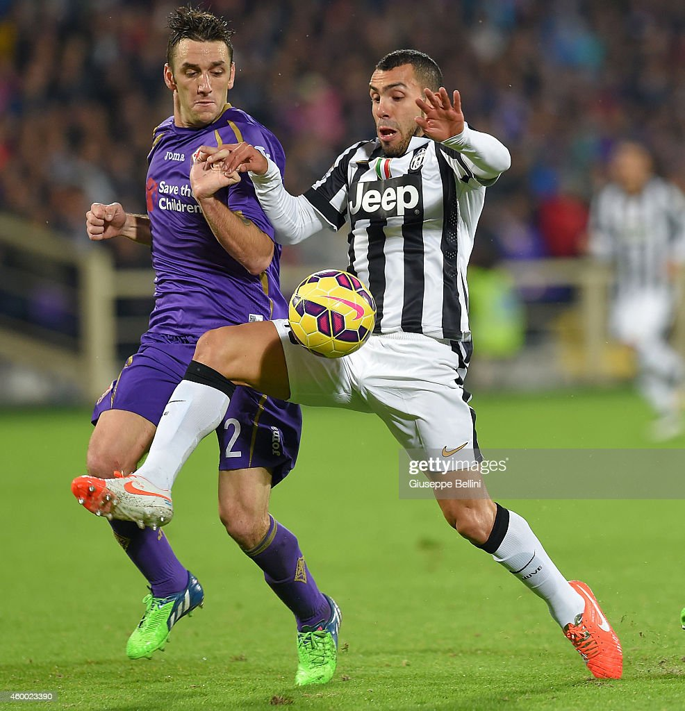 Gonzalo Rodriguez of ACF Fiorentina and Carlos Tevez of Juventus FC in action during the Serie A match between ACF Fiorentina and Juventus FC at Stadio Artemio Franchi on December 5, 2014 in Florence, Italy.