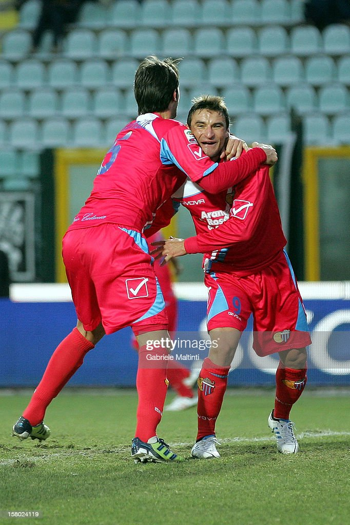 Gonzalo Ruben Bergessio (R) of Calcio Catania celebrates with team-mate <a gi-track='captionPersonalityLinkClicked' href=/galleries/search?phrase=Nicola+Legrottaglie&family=editorial&specificpeople=660919 ng-click='$event.stopPropagation()'>Nicola Legrottaglie</a> after scoring a goal during the Serie A match between AC Siena and Calcio Catania at Stadio Artemio Franchi on December 9, 2012 in Siena, Italy.