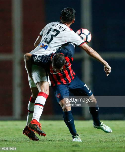 Gonzalo Ruben Bergessio of San Lorenzo fights for the ball with Paulo Andre of Atletico Paranaense during a group stage match between San Lorenzo and...